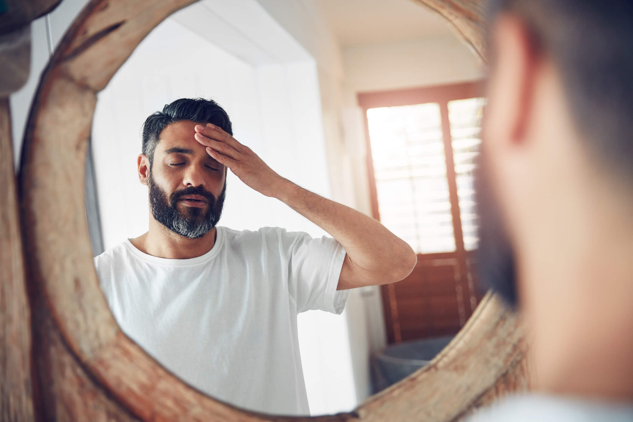 man tired looking in mirror