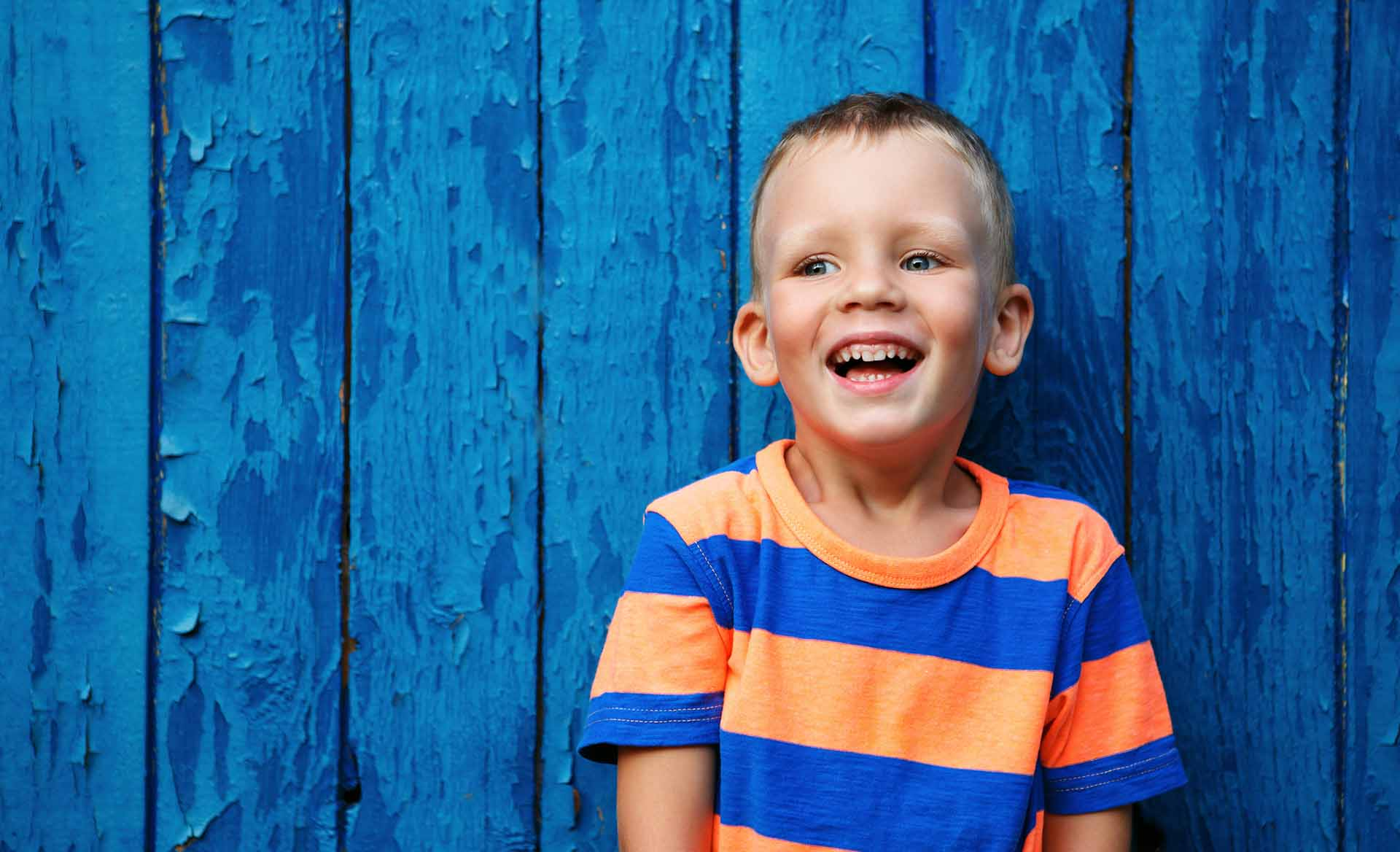 Portrait of happy joyful beautiful little boy against the old textured blue wall
