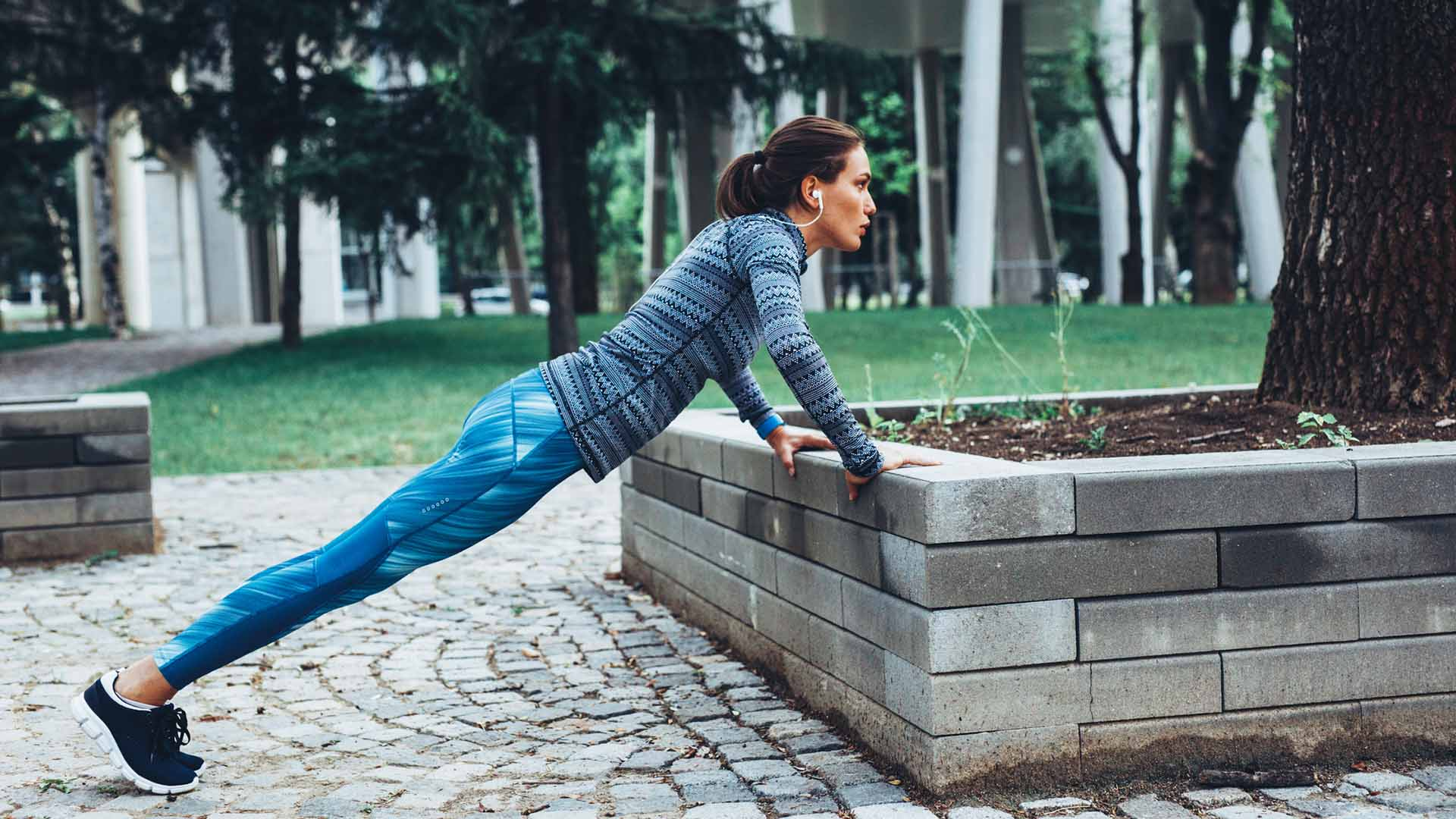 Woman doing pushups outdoor in the city.