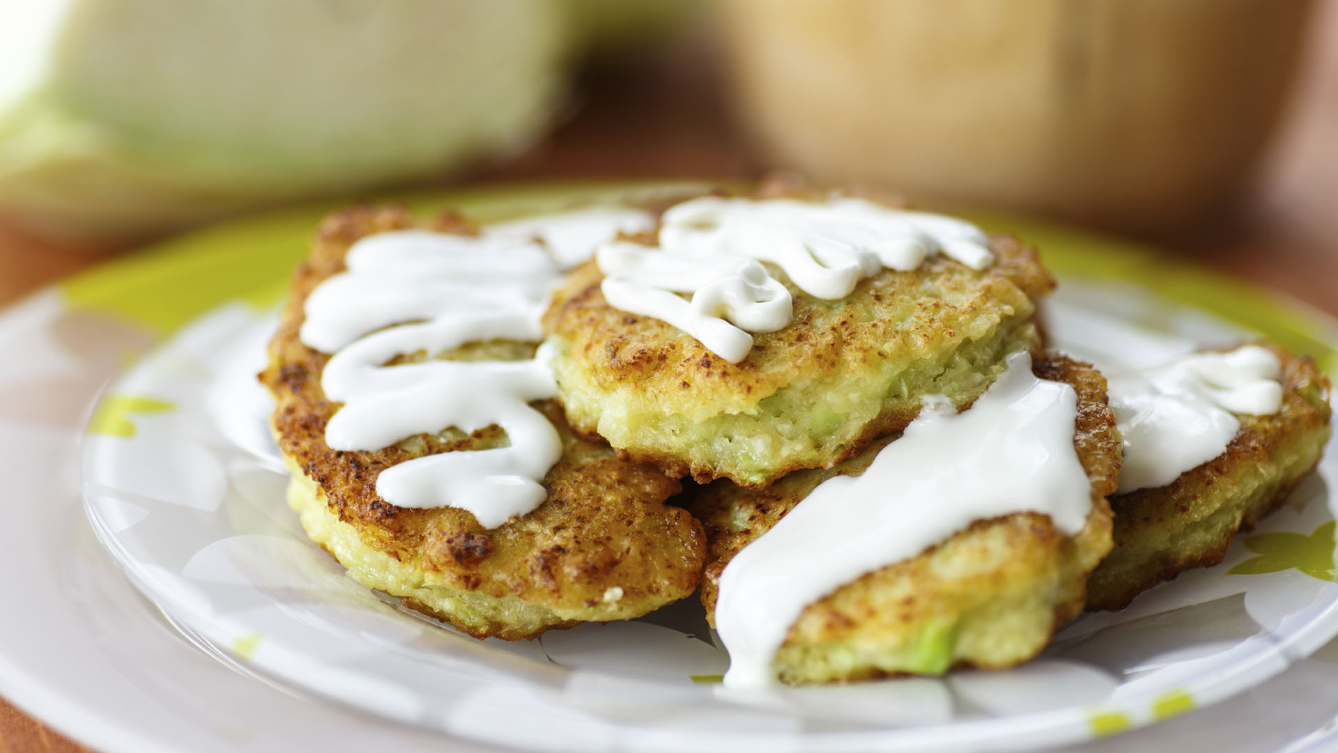 cabbage pancakes with sour cream on a plate