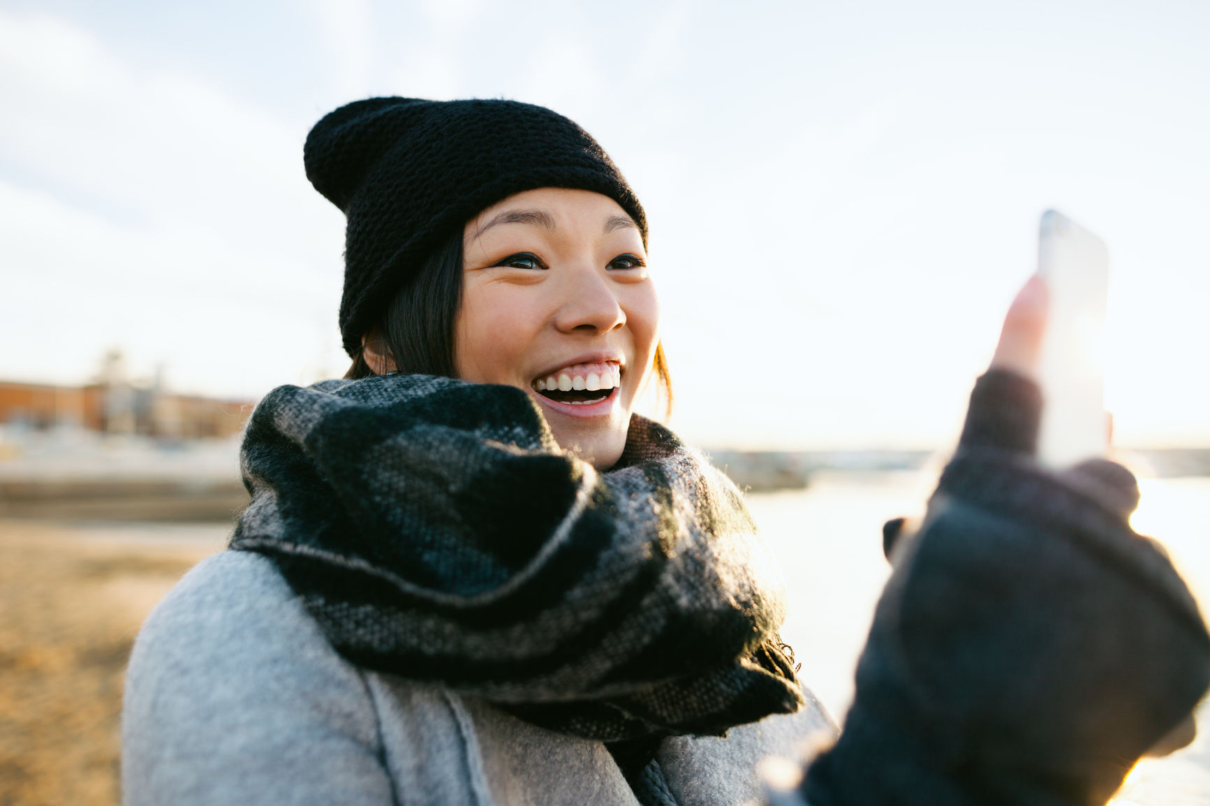 young woman looking at phone smiling outdoors
