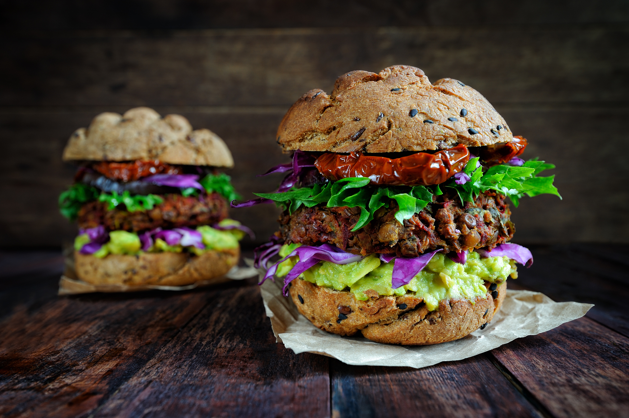 Fresh beetroot lentil vegan burger with grilled eggplant, sun-dried tomatoes and guacamole sauce