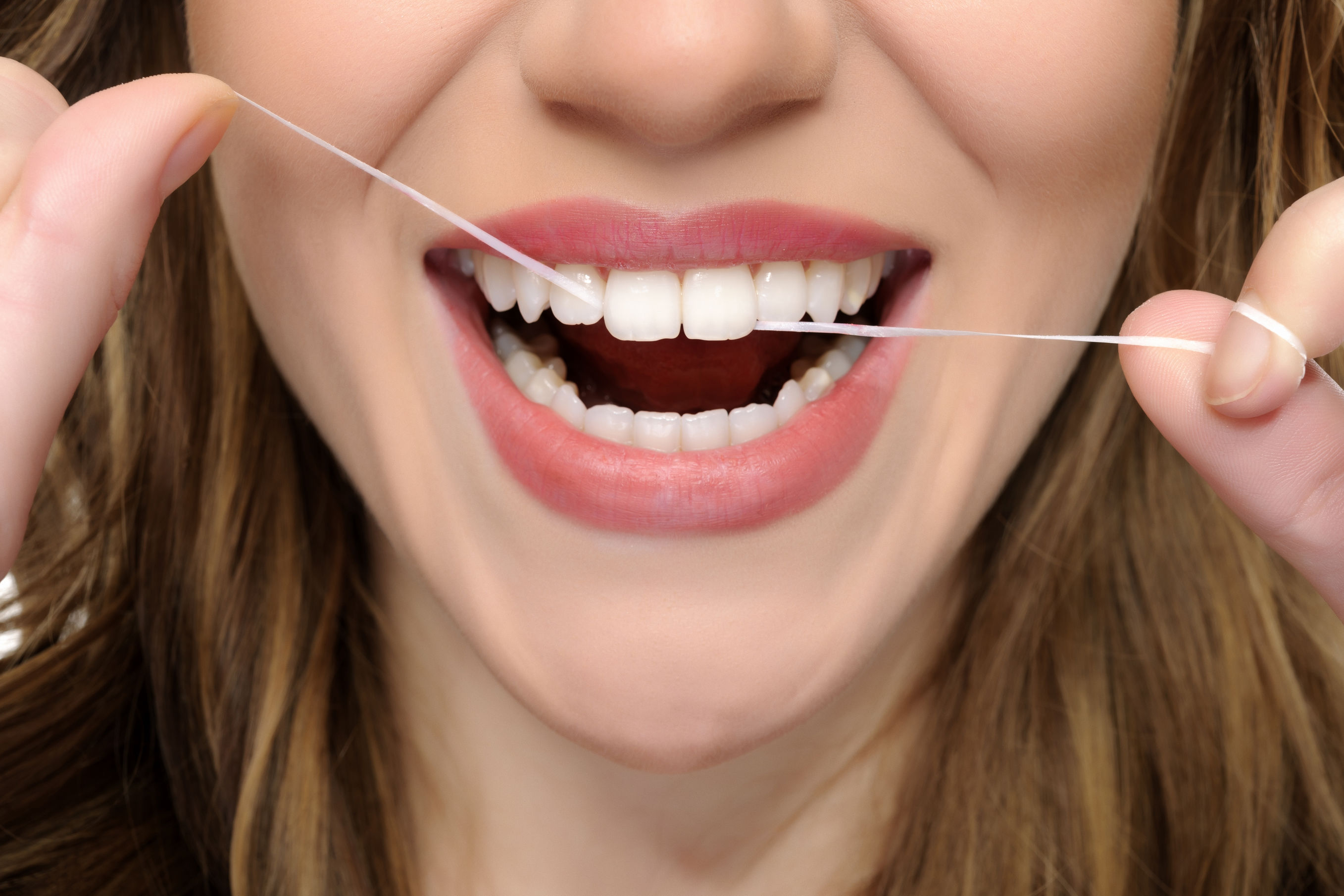 young woman mouth flossing her teeth.