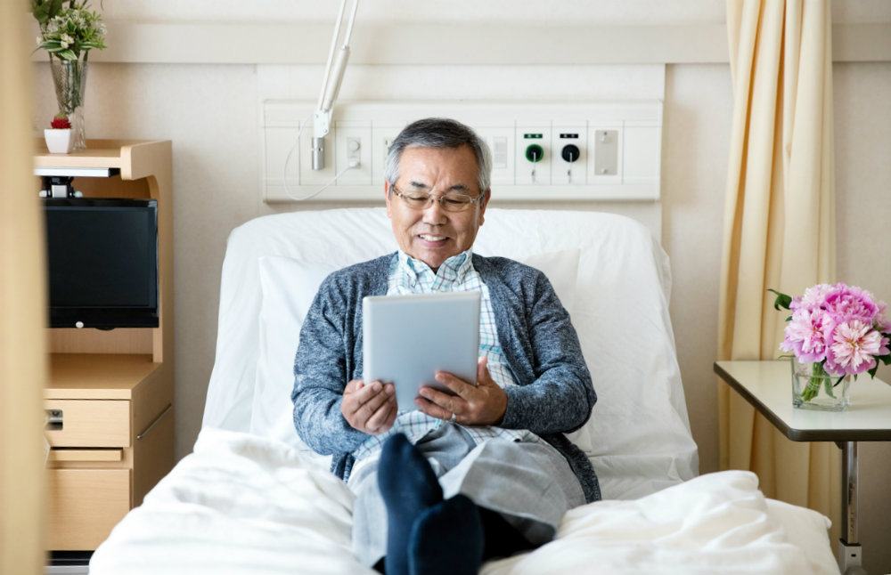 A patient relaxing on hospital bed reading